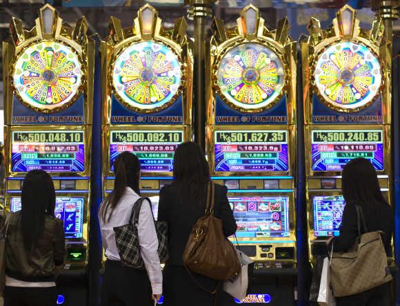 Women play slot machines at the Venetian Macao-Resort-Hotel in Macau.