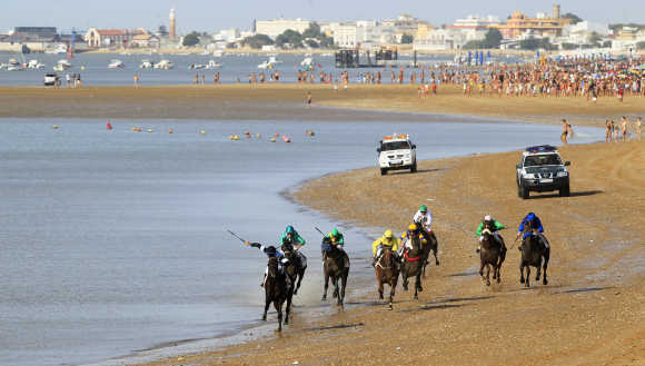 Jockeys take part in a race along the beach during low tide in Spanish town of San Lucar de Barrameda.