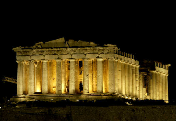 The ancient temple of the Parthenon is illuminated on the Acropolis Hill in Athens.