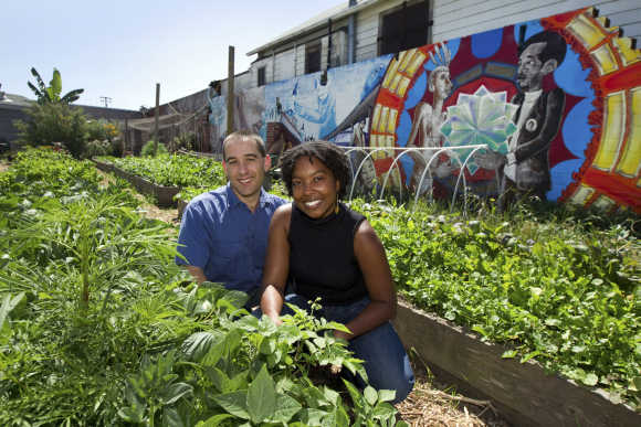 Braham Amadi and Nikki Henderson pose in a community garden behind a low-income housing development in Oakland, California.