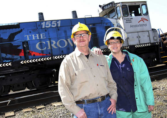 ArcelorMittal Mill employees Ed Goans stands with his daughter Kathleen Wilmink, as a ArcelorMittal train passes by, in Cleveland, Ohio.
