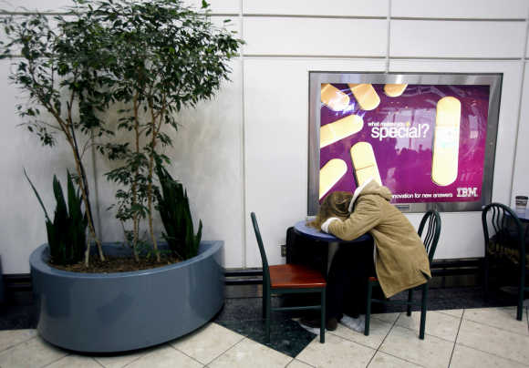 A woman sleeps on a table, a day before Thanksgiving, at the Newark International Airport in Newark, New Jersey.