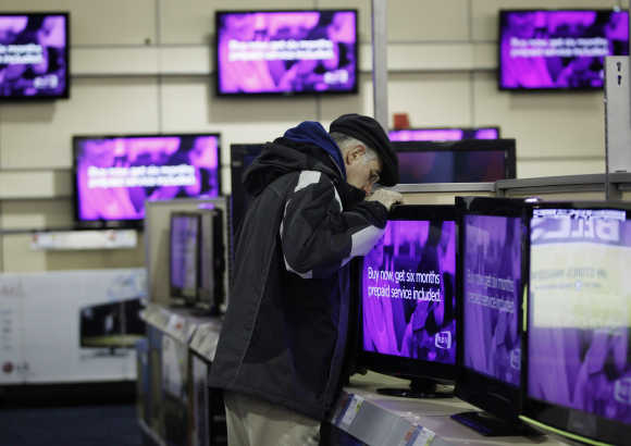 A man looks at a flat screen television at a Best Buy store in Flushing, New York.