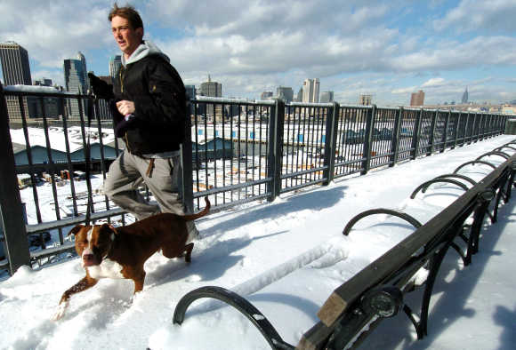 A jogger and his pit bull run along the snow-covered Brooklyn Promenade, across the East River from Manhattan, New York.
