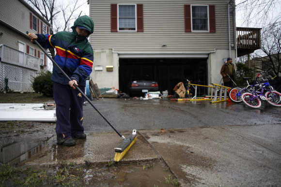Pablo Martinez cleans up mud in front of his home in Mamaroneck, New York.