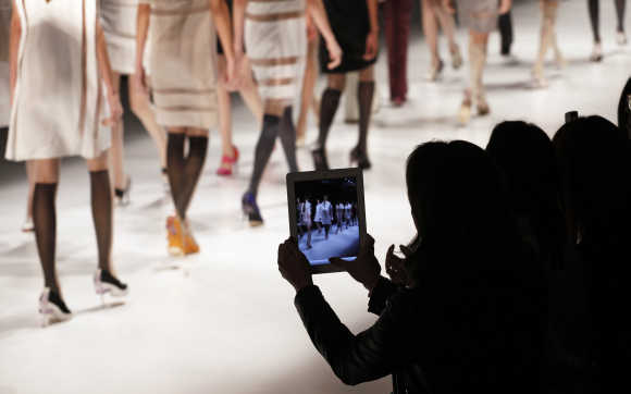 A spectator uses an iPad to record Gloria Coelho's Summer 2012/2013 collection during Sao Paulo Fashion Week.