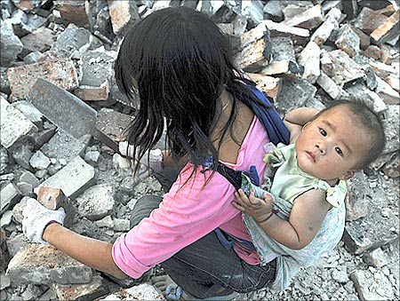 A migrant worker collects bricks as she carries her child on her back, at a demolition site in Jiaxing, Zhejiang province.