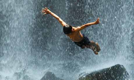 A boy jumps into the Llanos del Cortes waterfall in Bagaces, Costa Rica
