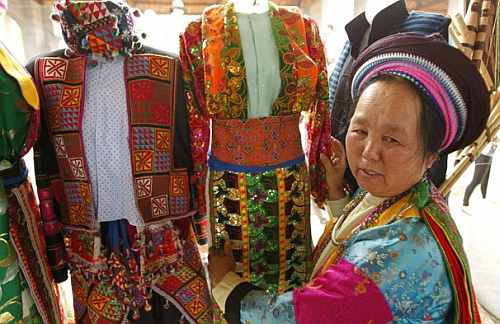 A Hmong woman displays traditional costumes for sale at the Vietnamese cultural village of Dong Mo, outside Hanoi