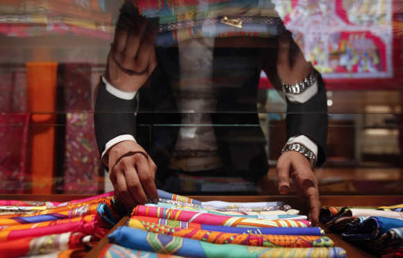 A saleswoman arranges scarves inside a Hermes showroom in Mumbai.