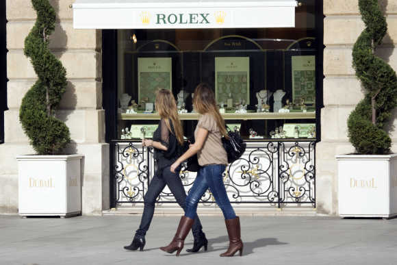 Women walk past a window display of luxury goods maker Rolex in Paris' Place Vendome.