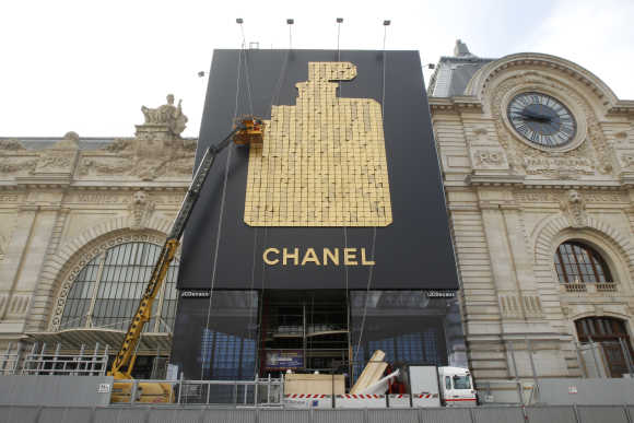 A crane removes a huge advertisement for Chanel No. 5 perfume installed on the facade of the Musee d'Orsay in Paris.