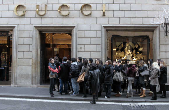 Shoppers wait for the opening of Gucci shop in downtown Rome.