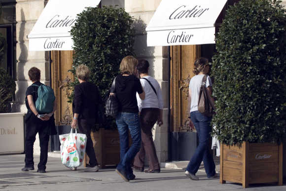 People look at a window display of luxury goods maker Cartier in Paris' Place Vendome.