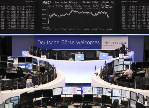 Traders work at their desks in front of the DAX board at the end of the session at Frankfurt stock exchange.
