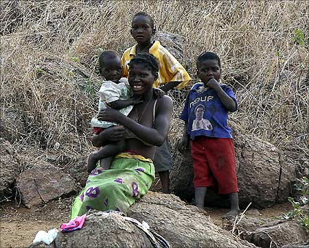 A local woman waits with her children for her husband to return from fishing in the Cahora Bassa dam in Tete province.