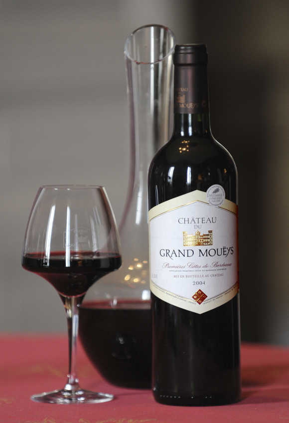 A carafe, a glass and a bottle of Chateau du Grand Moueys red wine are displayed in the tasting room of the Chateau in Capian, France.
