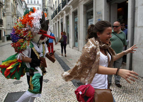 A reveler from the Portuguese village of Aveiro playfully chases a tourist during the Iberian Mask parade in Lisbon.