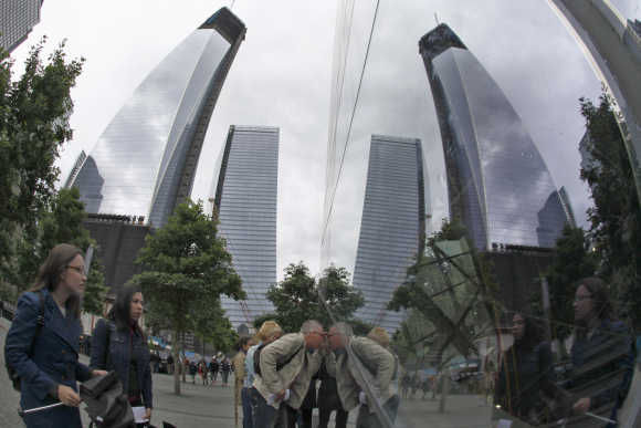 One World Trade Center is reflected inside a window as tourists peer through at the 9/11 Memorial Plaza in New York.