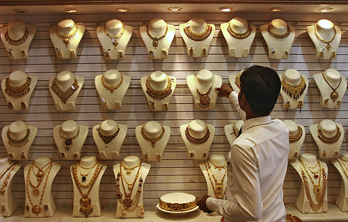 A salesman arranges a gold necklace inside a gold jewellery showroom in Kochi.