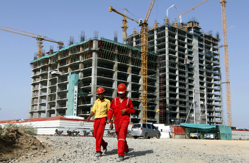 Workers walk in front of a multi-story commercial building under construction on the outskirts of Ahmedabad.
