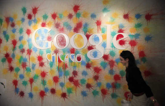 A woman walks past the Google Chicago headquarters logo in Chicago.