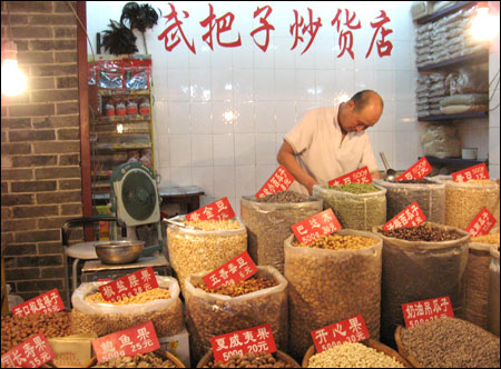A seller arranges nuts in a market on East Street, of Xi'an.