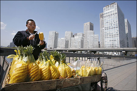 A vendor slices pineapple along the sidewalk in the central business district of Beijing.