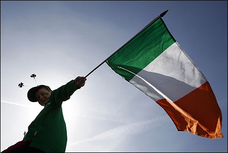 A boy holds a Republic of Ireland flag during a St Patrick's day march.