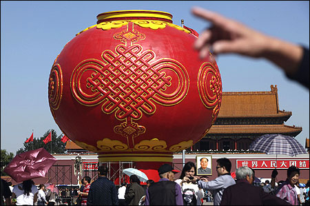 Tourists walk around a giant red lantern on display at Tiananmen Square for the National Day celebrations.