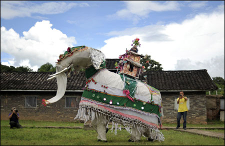 Tourists take pictures at the white elephant dance folk performance at a tourism resort in Jinggu county, Yunnan province.