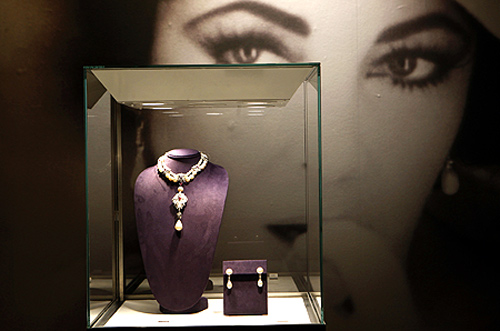 A photograph of Elizabeth Taylor is seen behind jewels on display.