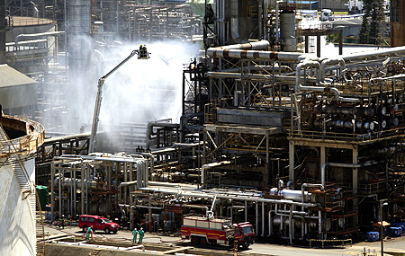 Fire fighters extinguish a fire at the Engen oil refinery in Durban.