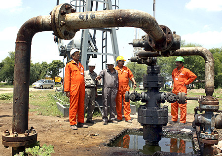 Engineers of Oil and Natural Gas Corp (ONGC) stand inside the Kalol oil field in Gujarat.