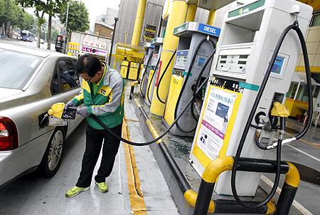 An employee fills the tank of a car at a petrol station in Seoul.