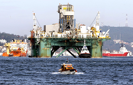 A fishing boat passes in the foreground as the Leiv Eiriksson, an oil drilling platform, makes its way through the Bosphorus in Istanbul.