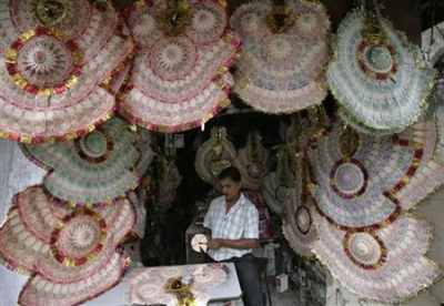 A shopkeeper staples rupee notes to make garlands at a market.