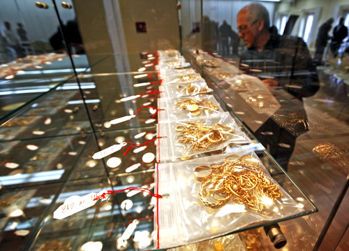 A man looks at jewels displayed for auction after being pawned by their owners at the Credit Municipal public pawnbroker in Nice.