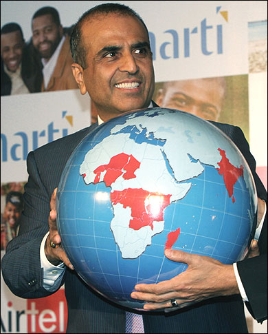 Chairman of Bharti Airtel Ltd Sunil Mittal holds a globe during a news conference.