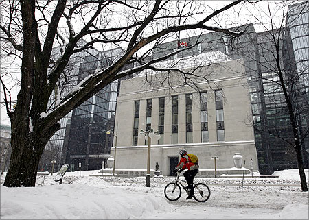 A cyclist passes the Bank of Canada building through a snow covered sidewalk in Ottawa.