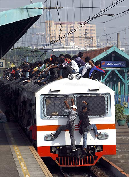 Passengers sit on the rooftop of a commuter train as it arrives at the Manggarai train station in Jakarta.