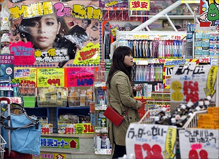 A woman looks through products at a drug store in Tokyo.
