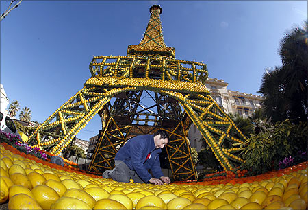 A worker puts the final touch at a sculpture featuring the Eiffel tower made from lemons and oranges during the lemon festival in Menton, southern France.