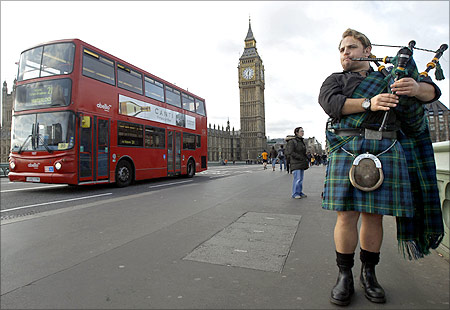A busker plays bagpipes for tourists near the Houses of Parliament in London.