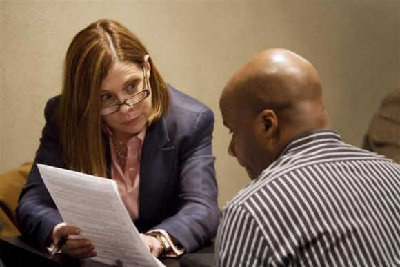 A job seeker listens to career coach Jane Cranston during a resume counselling session at a job fair in New York.