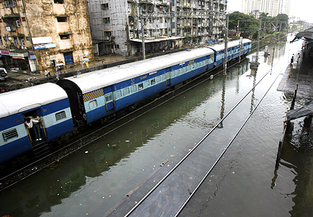 A train runs on flooded tracks on a rainy day in Mumbai.