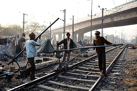 Indian labourers work on the tracks at Nizamuddin Railway Station.