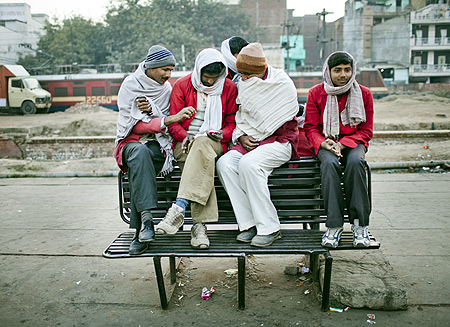 Workers take a break from unloading cargo from incoming trains at Nizamuddin Railway Station.