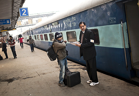 A passenger checks his seating on the Amritsar bound train, as he receives help from a conductor.