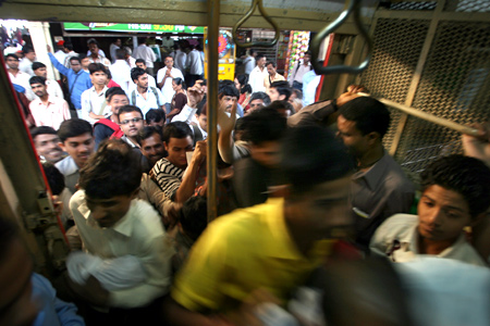 Commuters rush into a suburban train at a railway station in Mumbai.